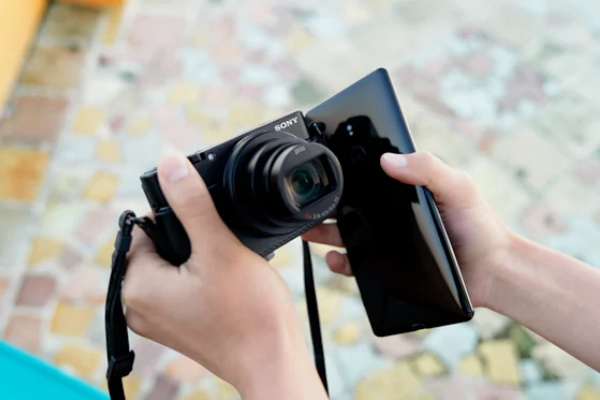 Picture of sony RX100 V camera beside phone