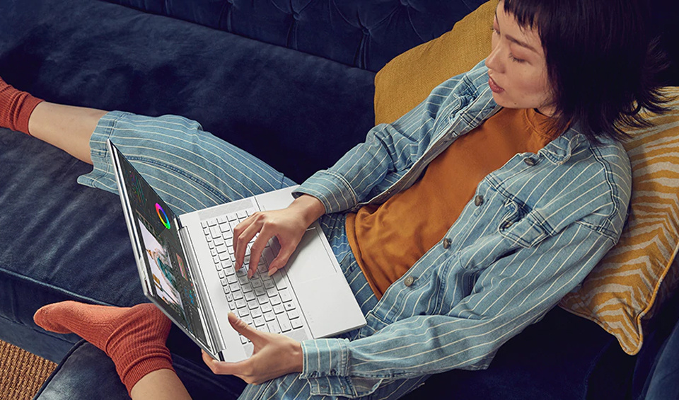 A woman uses the HP Envy x360 Ultrabook on a couch